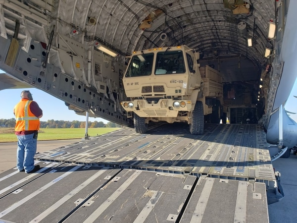 Richard Wolfe, a unit movement coordinator, provides directions as Pfc. Emmanuel Cook, of the 89th Military Police Brigade, loads a Light Medium Tactical Vehicle on a C-17 aircraft Oct. 29, 2018. The soldiers are deploying to the southwest border region to support and enable Department of Homeland Security and other law enforcement agencies. (Staff Sgt. Nathan Akridge/Army)
