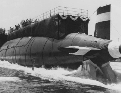 The submarine Thresher enters the water for the first time during launching ceremonies at the Portsmouth Naval Shipyard, Kittery, Maine, on July 9, 1960. It sank less than three years later during deep submergence tests off the coast of New England, killing 112 crew members and 17 civilians. (Naval History and Heritage Command)