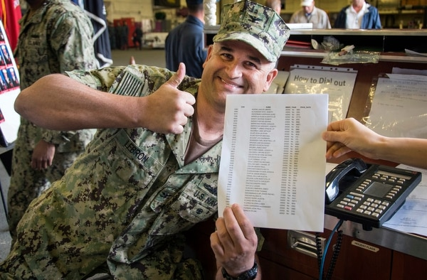 Capt. Richard Lebron, executive officer of the amphibious assault ship Bonhomme Richard, poses with the list of sailors who will advance to the next pay grade as a result of the spring 2018 advancement exam. (MC2 Diana Quinlan/Navy)