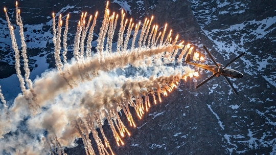 Super Puma Cougar helicopter releases flares over Brienz in the Bernese Alps on October 10, 2018, during the annual live fire event of the Swiss Air Force at the Axalp. - At an altitude of 2,200 meters above sea level, spectators attended a unique aviation display performed at the highest air force firing range in Europe. (FABRICE COFFRINI/AFP/Getty Images)