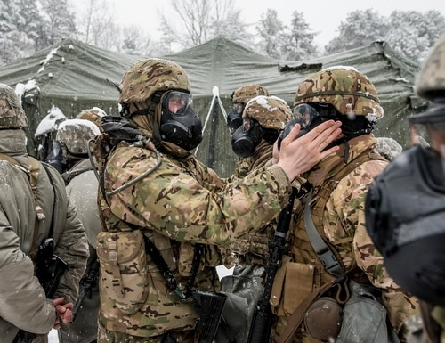 Sgt. Logan Hall, a U.S. Army Reserve soldier with the 200th Military Police Command, inspects the seal of a protective mask during formation during a field training exercise at Fort Meade, Md., Jan. 13, 2019. (Master Sgt. Michel Sauret/Army Reserve)