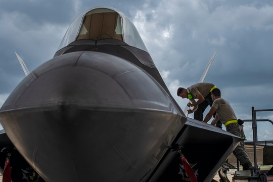 Airmen from the 325th Maintenance Squadron perform maintenance on an F-22 Raptor at Eglin Air Force Base, Florida, July 18, 2019. (Airman 1st Class Emily Smallwood/Air Force)