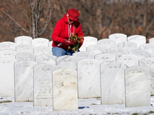A visitor places a bouquet of flowers at a grave in Fort Logan National Cemetery in Sheridan, Colo., on Nov. 10, 2020. (David Zalubowski/AP)