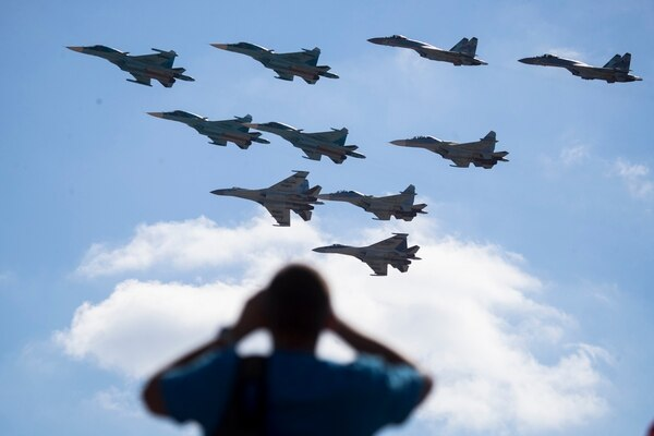 A man watches Russian military jets performing on Aug. 12, 2017, in Alabino, outside Moscow, Russia. The Russian military says major war games, the Zapad (West) 2017 maneuvers, set for next month will not threaten anyone. (Pavel Golovkin/AP)