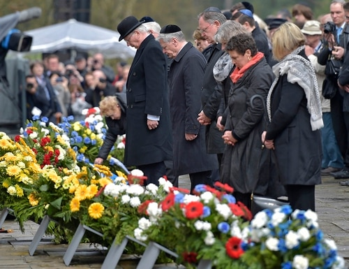 The Duke of Gloucester, left, and German President Joachim Gauck, second left, lay flowers at a mourning wall during a ceremony to mark the 70th anniversary of the liberation of the Bergen-Belsen concentration camp in Bergen, northern Germany, Sunday, April 26, 2015. More than 52,000 people died in the Nazi terror in Bergen-Belsen, among them the famous teenage diarist Anne Frank, until British troops liberated the camp in April 1945. (AP Photo/Martin Meissner)