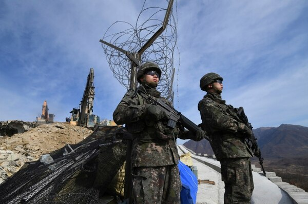 South Korean soldiers stand guard as construction equipment destroys a guard post in Cheorwon along the Demilitarized Zone dividing the two Koreas on Thursday, Nov. 15, 2018. Relations between the Koreas have improved this year, with the North entering disarmament talks with a vague promise to achieve complete denuclearization of the Korean Peninsula. (Jung Yeon-je/Pool Photo via AP)