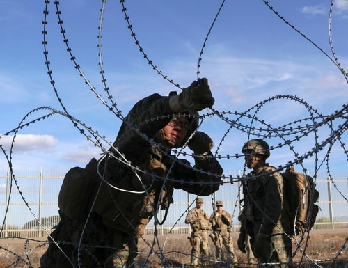 U.S. Marines install razor wire next to the U.S.-Mexico border fence on Dec. 2, 2018 as seen from Tijuana, Mexico. President Donald Trump says the U.S. has caught 10 terrorists coming into the U.S. recently. But these 10 do not exist, except as a federal statistic he used to describe emigrants from Mexico as a menace, government reports show. (John Moore/Getty Images)