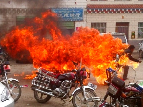 "A Tibetan runs in flames in his self-immolation to protest against Chinese rule, on a street in Yushu prefecture in China's Qinghai province on June 20, 2012. China says it will not ""renounce the use of force"" in efforts to reunify Taiwan with the mainland and vows to take all necessary military measures to defeat ""separatists"" in Tibet. (The Tibetan Youth Congress via AP)"
