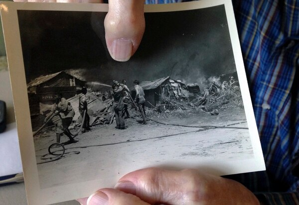 In this Tuesday, Nov. 21, 2017, photo, World War II veteran Kenneth F. Lincoln, 90, points to himself in a photo that was taken when he was serving in the U.S. Navy and fighting a large fire that broke out among straw huts in Rabat, Morocco, in the summer of 1946. (Jennifer McDermott/AP)