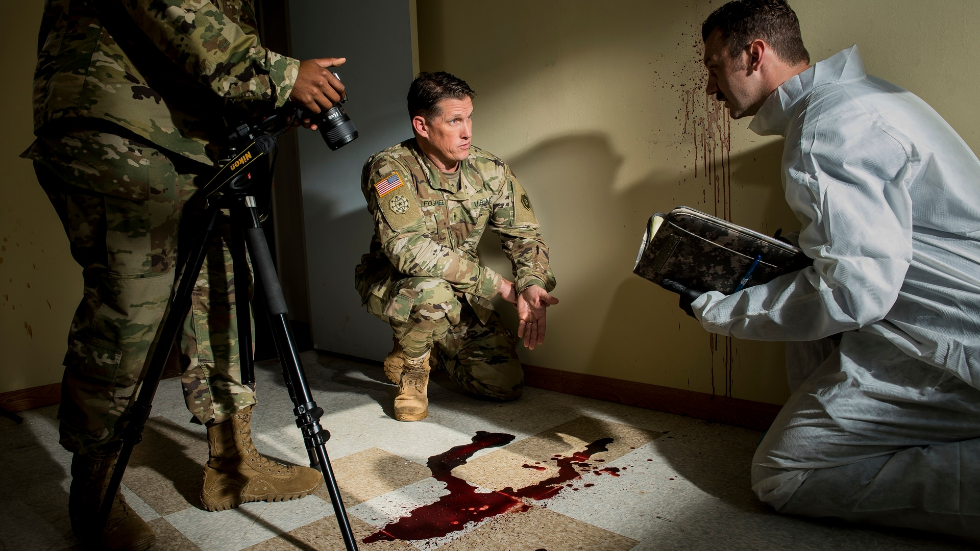 An Army special agent poses in a staged crime scene at Fort Belvoir, Virginia, as part of a photo shoot designed to promote and recruit warrant officers in the CID career field. (Master Sgt. Michel Sauret/Army)