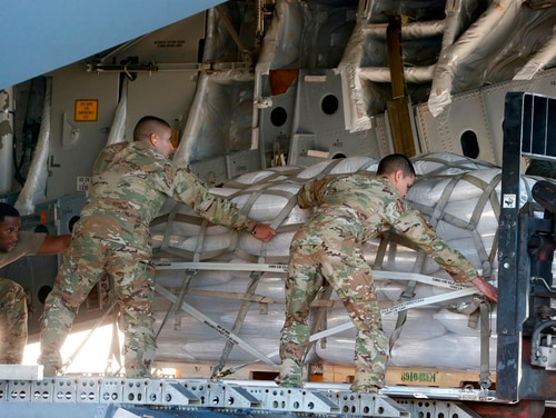 US soldiers load a C-17 cargo plane with food, water and medicine for a humanitarian mission to Venezuela, at Homestead Air Force Base in Homestead, Florida, on February 22, 2019. (RHONA WISE/AFP/Getty Images)