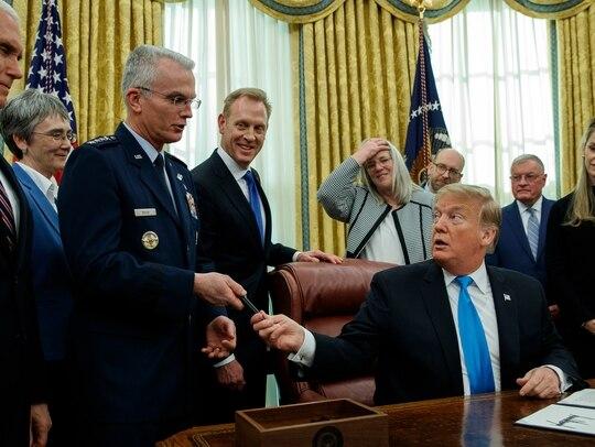 President Donald Trump hands a pen to Air Force Gen. Paul Selva after signing