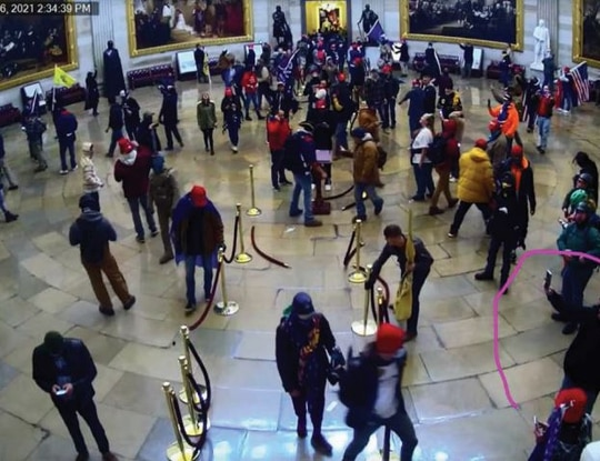 CCTV footage from inside the Capitol on Jan. 6, 2021, shows former Army Capt. Gabriel A. Garcia, according to the FBI. He is identified in a circle and can be seen holding up a phone and recording a video. (DoJ)