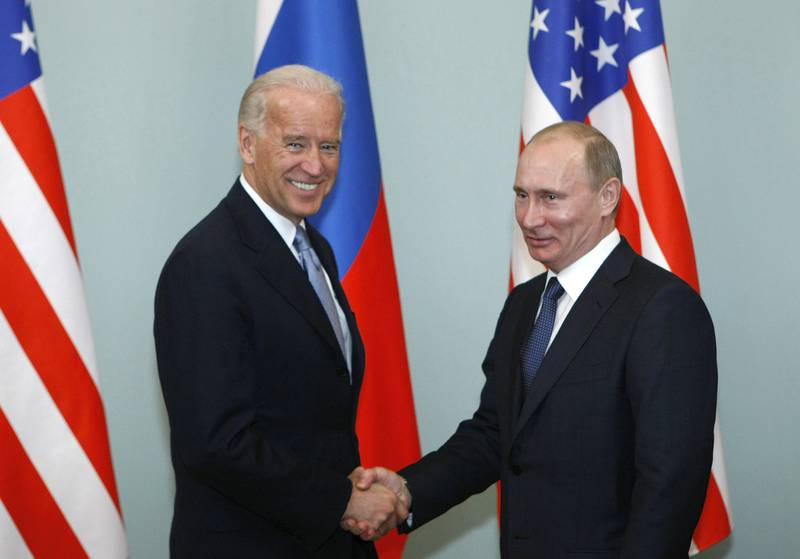 In this March 10, 2011, file photo, then-Vice President Joe Biden, left, shakes hands with Russian Prime Minister Vladimir Putin in Moscow.