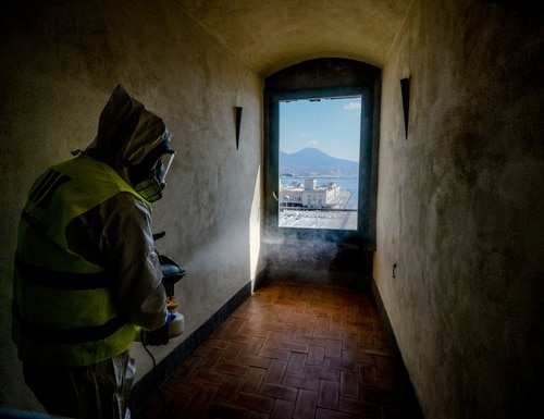 A worker sprays disinfectant to combat coronavirus in the museum hosted by the Maschio Angioino medieval castle, in Naples, Italy, on March 10. (Alessandro Pone/LaPresse via AP)