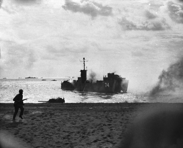 In this handout from the U.S. Marine Corps, a smoking LSM (Landing Ship Medium) moves out from the beach after taking two direct hits from Japanese artillery on the island of Iwo Jima, March 2, 1945. The ship managed to safely unload its cargo of Marine tanks. (U.S. Marine Corps/AP)