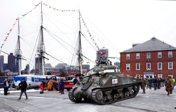 World War II tank gunner Clarence Smoyer sits atop a tank as he passes the historic frigate U.S.S. Constitution at the Charlestown Naval Shipyard in Boston on Wednesday. (Charles Krupa/AP)
