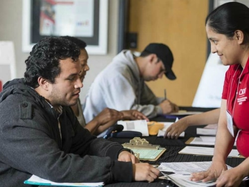 A student volunteer at California State University, Northridge's VITA Clinic helps a taxpayer with tax preparation at the David Nazarian College of Business and Economics. (Photo provided by CSUN)