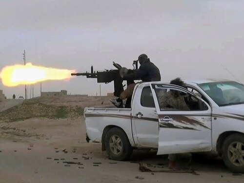 This frame grab from video posted online Jan. 18, 2019, by supporters of the Islamic State group, purports to show an ISIS fighter firing a weapon during clashes with members of the U.S.-backed Syrian Democratic Forces, in the eastern Syrian province of Deir el-Zour, Syria. (Militant Photo via AP)