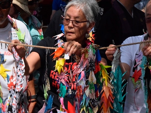 Satsuki Ina, 75, hangs origami cranes as part of the Tsuru for Solidarity protest of child detention at Fort Sill U.S. Army post, during a healing ceremony at Shepler Park in Lawton, Okla., on June 22, 2019. (Scott Rains/The Lawton Constitution via AP)