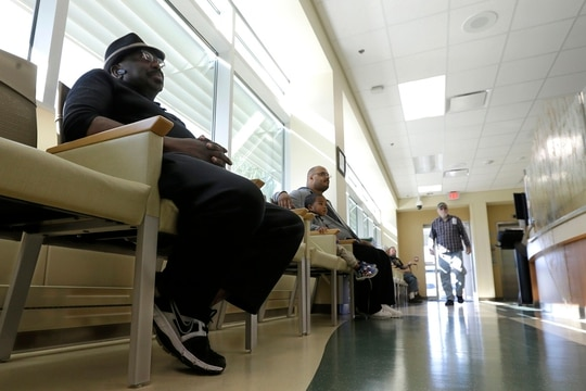 Navy veteran Samuel Ewing, left, waits to be seen by a medical care provider at the Sacramento Veterans Affairs Medical Center in Rancho Cordova, Calif., in April 2015. (Rich Pedroncelli/AP)