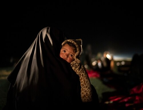 In this Feb. 25, 2019, file photo, a woman carries her baby at a screening center run by U.S.-backed Syrian Democratic Forces after being evacuated out of the last territory held by Islamic State militants, outside Baghouz, Syria. (Felipe Dana/AP)