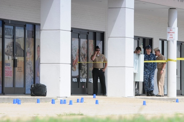 Reserve Recruitment personnel stand outside a Navy recruiting building as the area is cordoned off with blue shell casing markers in the parking lot on Thursday, July 16, 2015 in Chattanooga, Tenn. At least two military facilities in Tennessee were attacked in shootings Thursday, including one at a Navy recruiting building, officials said. (Tim Barber/Chattanooga Times Free Press via AP) THE DAILY CITIZEN OUT; NOOGA.COM OUT; CLEVELAND DAILY BANNER OUT; LOCAL INTERNET OUT; MANDATORY CREDIT