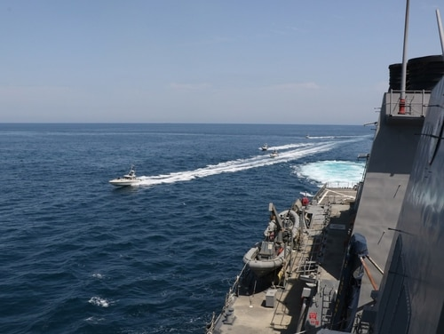In this April 15, 2020, photo, Iranian Revolutionary Guard vessels sail close to U.S. military ships in the Persian Gulf near Kuwait. (U.S. Navy via AP)