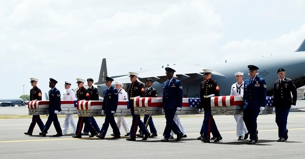 Military members carry transfer cases from a C-17 at a ceremony marking the arrival of the remains believed to be of American service members who fell in the Korean War at Joint Base Pearl Harbor-Hickam in Hawaii, Wednesday, Aug. 1, 2018. North Korea handed over the remains last week. (Susan Walsh/AP)