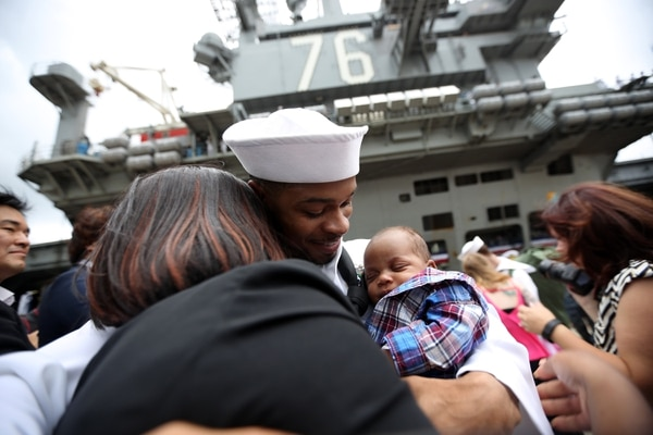 Crew members of U.S. navy nuclear-powered aircraft carrier USS Ronald Reagan reunite their loved ones upon arrival at the U.S. Navy's Yokosuka base in Yokosuka, south of Tokyo Thursday, Oct. 1, 2015. The USS Ronald Reagan has entered its new home in Japan's Yokosuka naval port, replacing its predecessor USS George Washington. The arrival Thursday comes as Tokyo tries to deepen defense ties with the U.S. under new security law that expand the role of Japan's military. (AP Photo/Eugene Hoshiko)
