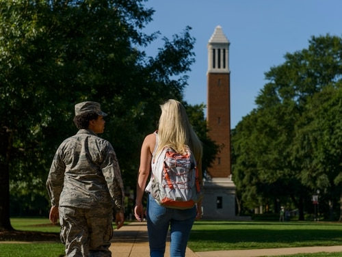 A service member and military dependent walk on the campus of the University of Alabama. Military and veteran students using the GI Bill to pay for college will likely be shielded from the brunt of a government shutdown if Congress does not come to a budget agreement by midnight Jan. 20. (University of Alabama)