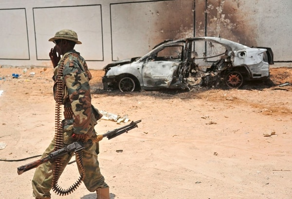 A Somali soldier patrols next to the burnt-out wreckage of a car that was used by suspected al-shabab fighters on April 16, 2017. Somali security forces shot dead two suspected al-shabab militants, an Al-Qaeda linked extremist group, who were said to be involved in firing rockets. / AFP PHOTO / Mohamed ABDIWAHAB (Photo credit should read MOHAMED ABDIWAHAB/AFP/Getty Images)