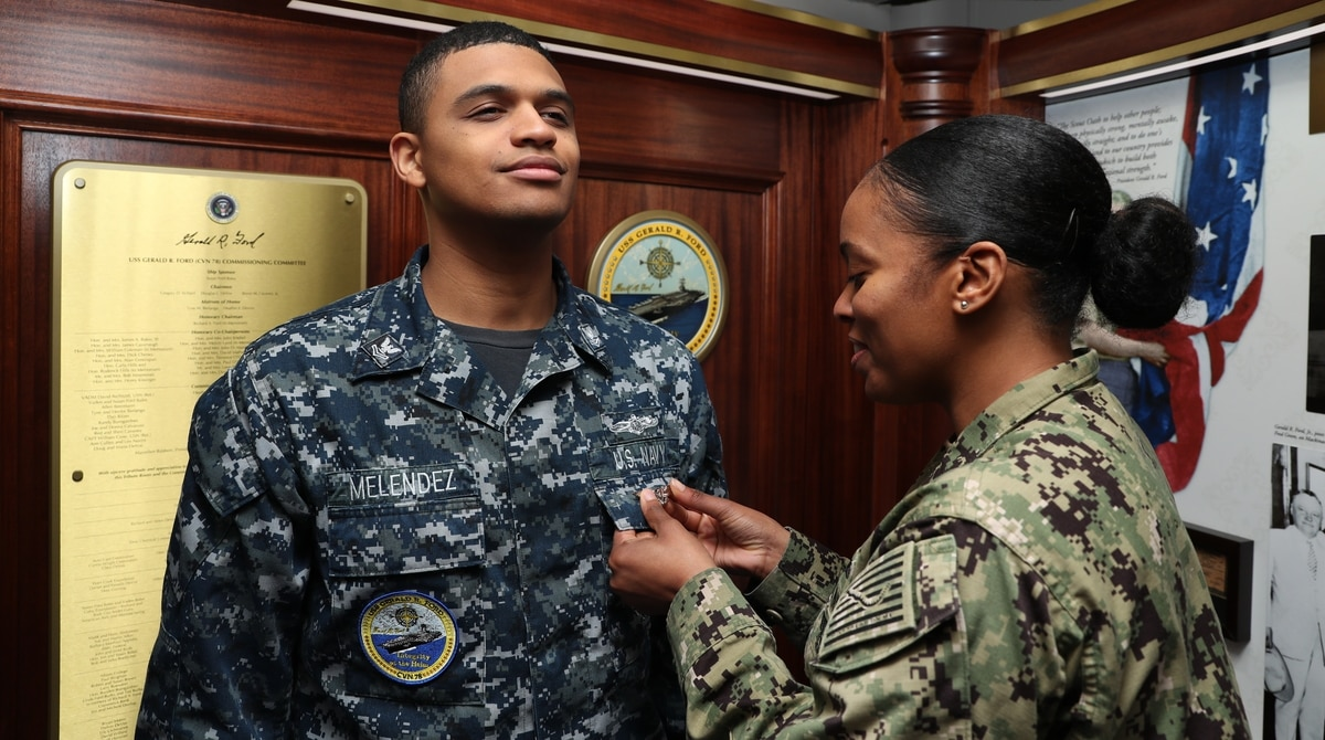 e69eea55 ... assigned to the aircraft carrier Gerald R. Ford's combat systems  department, receives his Enlisted Aviation Warfare Specialist pin during a  Jan.