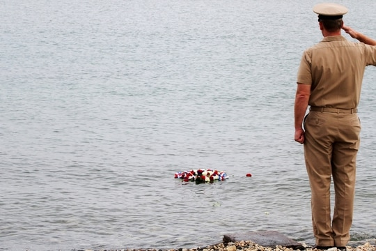 Navy Capt. John R. Nettleton holds his salute after he tossed a commemorative wreath into the bay during Naval Station Guantanamo Bay's 2014 ceremony remembering the Battle of Midway. He was convicted Friday on multiple charges tied to a civilian worker's 2015 death there. (Navy)