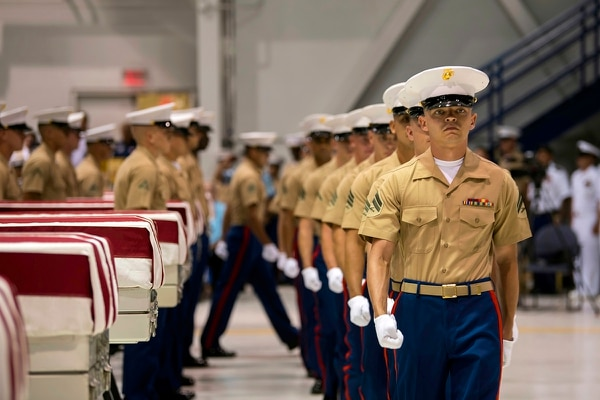 In this Wednesday, July 17, 2019, photo, Marines march past transfer cases carrying the possible remains of unidentified service members lost in the Battle of Tarawa during World War II in a hangar at Joint Base Pearl Harbor-Hickam in Hawaii. (Sgt. Jacqueline Clifford/Marine Corps via AP)