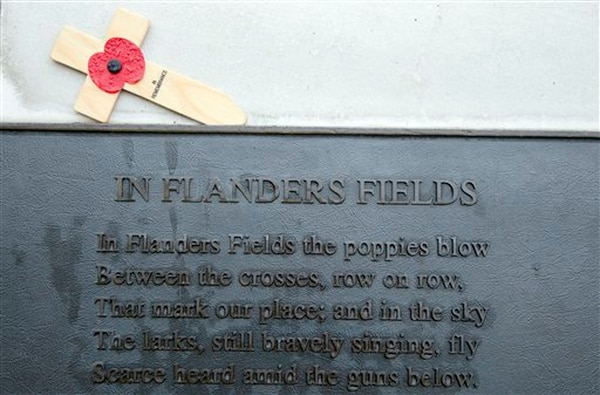 A red poppy adorns a wooden cross over a plaque with the poem 'In Flanders Fields' by John McCrae at Essex Farm in Boezinge, Belgium on Nov. 12, 2013.(Virginia Mayo/AP)
