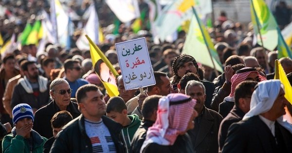 A Syrian Kurd marches with a sign reading in Arabic