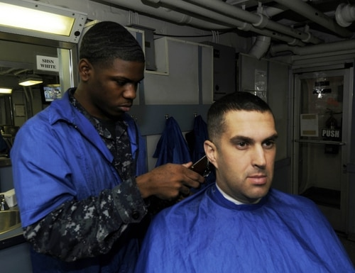 Chief Aviation Electronics Technician Kirk P. Killian, shown here getting a haircut as a petty officer first class in 2010, has been charged with conspiring with other chiefs to steal military gear. (Navy)
