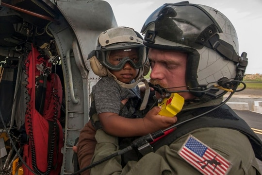 Naval Aircrewman (Helicopter) 2nd Class Brandon Larnard, assigned to Helicopter Sea Combat Squadron 22, carries an evacuee off an MH-60S Sea Hawk helicopter in 2017 following the landfall of Hurricane Maria on the island of Dominica. (Mass Communication Specialist 3rd Class Sean Galbreath/Navy)