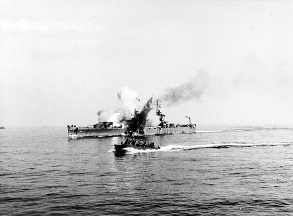 The light cruiser Savannah is hit by a German radio-controlled bomb, while supporting Allied forces ashore during the Salerno operation, 11 September 1943. The bomb hit the top of the ship's number three 6/47 gun turret and penetrated deep into her hull before exploding. The photograph shows the explosion venting through the top of the turret and also through Savannah's hull below the waterline. A motor torpedo boat passes by in the foreground. (Courtesy of the Naval Historical Foundation, Adm. H. Kent Hewett, now in the collections of U.S. Naval History and Heritage Command)