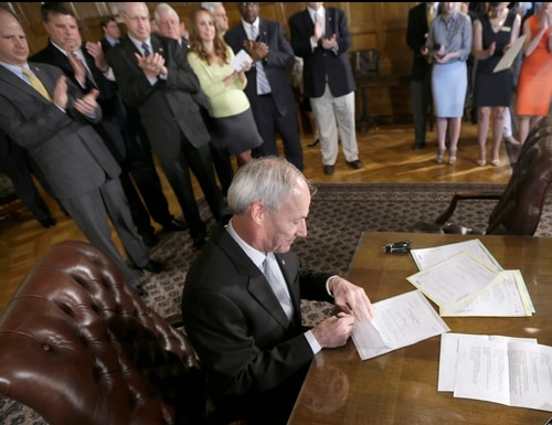 Arkansas Gov. Asa Hutchinson signs a bill at the Arkansas state Capitol in Little Rock, Ark., Friday, May 29, 2015. The governor signed multiple bill Friday including two to provide Lockheed Martin with a $87 million incentive package if it is the successful bidder for a military vehicle assembly contract. (AP Photo/Danny Johnston)