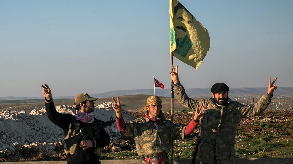 In this Feb. 22, 2015, file photo, Syrian Kurdish militia members of YPG make a V-sign next to poster of Abdullah Ocalan, jailed Kurdish rebel leader, and a Turkish army tank in the background in Esme village in Aleppo province, Syria. (AP Photo/Mursel Coban, Depo Photos, File)