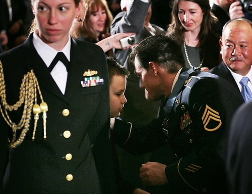 After receiving the Medal of Honor from President Obama, former active-duty Army Staff Sergeant Clinton Romesha greets MacAidan Gallegos, center, whose father, Army Sgt. Justin Gallegos, had served in the same regiment as Romesha and died in Afghanistan along with seven other soldiers in 2009. (Alex Wong/Getty Images)