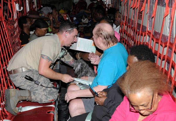 Air Force Staff Sgt. Jeffrey Mikulan, 71st Aircraft Maintenance Unit, helps evacuees with their seatbelt on Thursday at John Brooks Regional Airport in Beaumont, Texas. The 71st Rescue Squadron evacuated 111 individuals from Beaumont to Dallas. (Staff Sgt. Ian Hoachlander/Air Force)