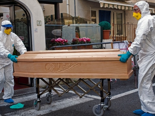 Medical staff wearing protective suits carry the coffin containing the body of Assunta Pastore, 87, after she passed away in her room at the Garden hotel in Laigueglia, northwest Italy, Liguria region, on March 1. The woman, part of a group of elderly tourist from the Lombardia region, tested positive for COVID-19. The hotel has been placed under quarantine as Italy continued to scramble to contain the spread of the corona virus. (AP)