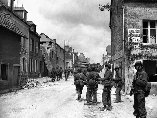 In this June 11, 1944, file photo, American paratroops patrol in the streets of Sainte-Mere-Eglise, France, before pushing on toward Cherbourg. About 15,000 paratroopers landed in and around the village not long after midnight on June 6, 1944, and seized it from the Germans by 4:30 a.m. (AP)