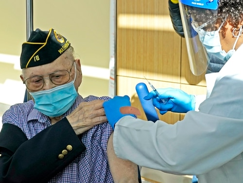 U.S. Army veteran Gene Moy, 103, of Seattle, receives the second shot of the Pfizer COVID-19 vaccination on Feb. 23, 2021, from a nurse at the VA Puget Sound Health Care System campus in Seattle. (Ted S. Warren/AP)