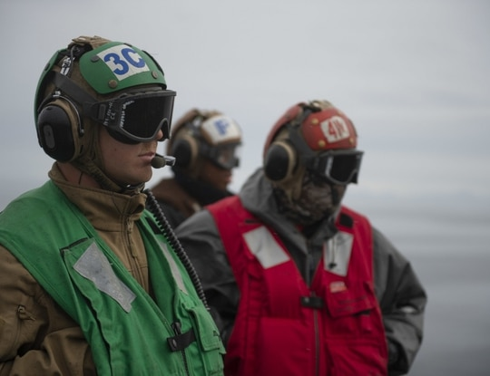 Chief Aviation Electronics Technician Justin Calderone, at left in 2019, died Thursday following a medical emergency aboard the aircraft carrier Theodore Roosevelt. (Navy)