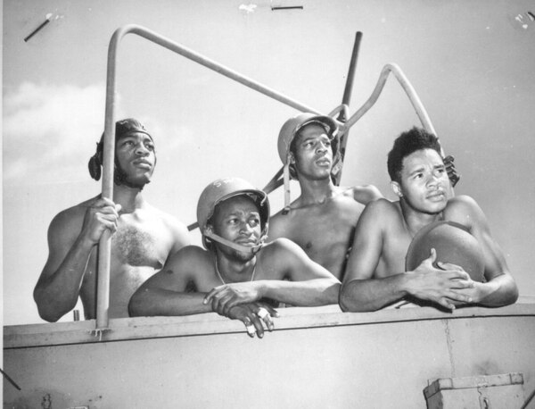 A crew of a 20mm gun on board a Coast Guard fighting ship are hanging up some new records for speed and accuracy. Left to right: Daniel Moore, Walter L. Bottoms, William Wheeler, and Rudolph C. Grimes, all second class steward's mates. (National Archives)
