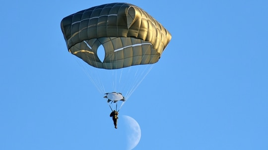 A U.S. Army paratrooper descends onto Juliet Drop Zone, Pordenone, Italy, after exiting an Air Force C-130 Hercules aircraft during airborne operations, Dec. 3, 2019. (Paolo Bovo/Army)